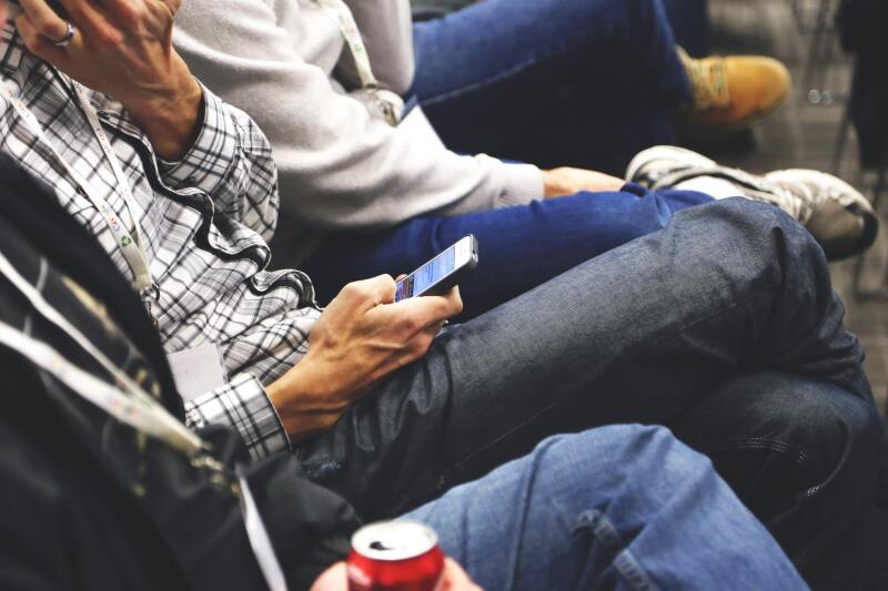image of man using smartphone during a meeting
