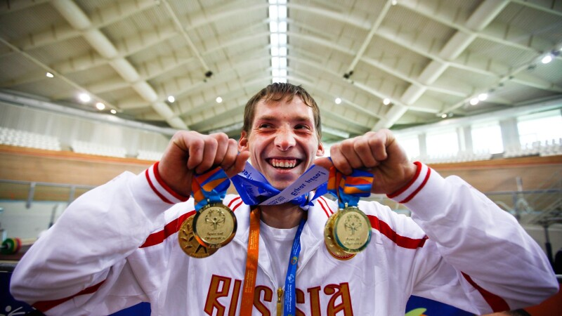Special Olympics participant holding medals